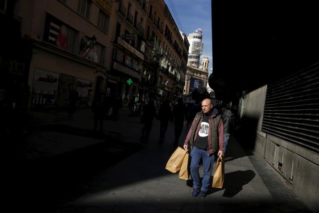 A man carries shopping bags in a shopping district in downtown Madrid, Spain, November 26, 2015. REUTERS/Susana Vera