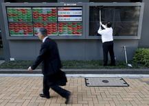 Un hombre limpiando unas pantallas afuera de una correduría en Tokio, Japón. 6 de abril de 2016. Las bolsas de Asia y el oro retrocedían el miércoles luego de que los mercados fueron sacudidos por reportes de que el Banco Central Europeo planea finalizar su programa de compra de activos. REUTERS/Issei Kato/Files