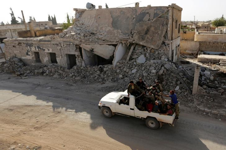 Rebel fighters ride on a pick-up truck past damaged buildings in the northern Syrian rebel-held town of al-Rai, in Aleppo Governorate, Syria, October 5, 2016. REUTERS/Khalil Ashawi