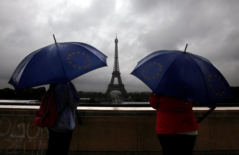 Tourists protect themselves from the rain under umbrellas in front of the Eiffel tower as they visit the French capital during summer holidays in Paris, France July 19, 2011.   REUTERS/Eric Gaillard/File Photo