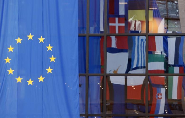 Flags are reflected in a window at the European Council building, a day before an E.U. heads of state summit in Brussels March 12, 2008.    REUTERS/Thierry Roge