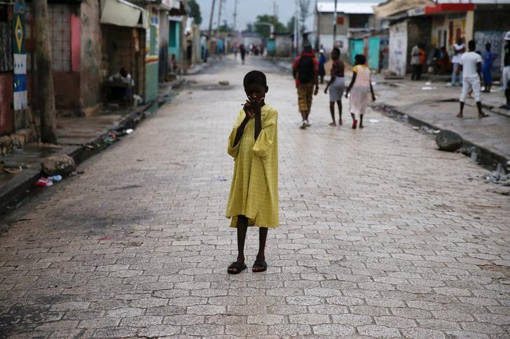 A child stands on a street, after Hurricane Matthew passes Cite-Soleil in Port-au-Prince, Haiti, October 5, 2016. REUTERS/Carlos Garcia Rawlins