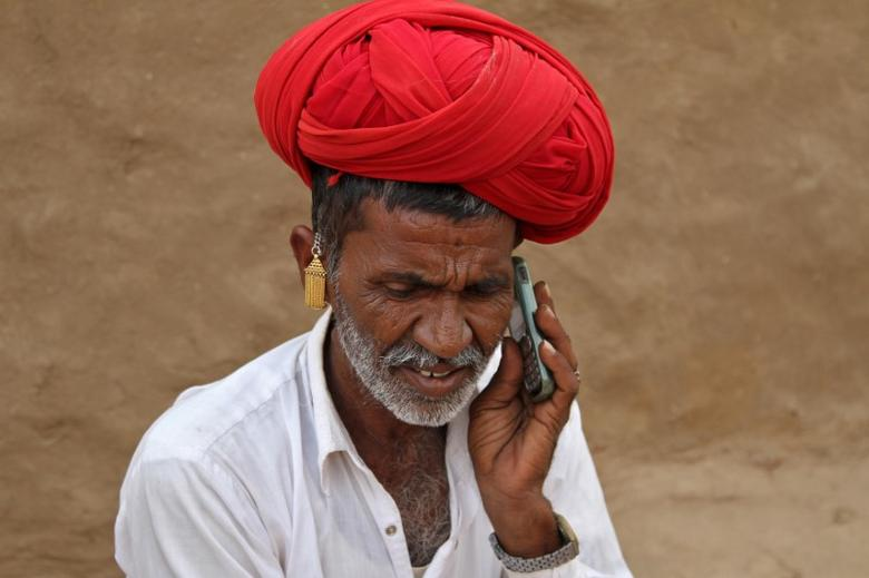 A man talks on his mobile phone in the village of Devmali in the desert state of Rajasthan, June 14, 2016. REUTERS/Himanshu Sharma/Files