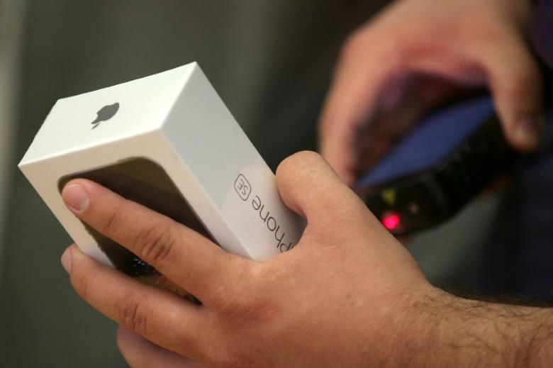 A customer buys the new iPhone 7 smartphone inside an Apple Inc. store in Los Angeles, California, U.S., September 16, 2016. REUTERS/Lucy Nicholson - RTSO2WB