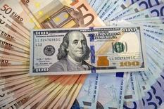 Банкноты доллара США и евро. Сараево, 9 марта 2015 года. Крупнейший золотодобытчик России Полюс по новой дивидендной политике будет раз в полгода выплачивать 30 процентов от прибыли до вычета процентов, налогов, амортизации и износа (EBITDA) при условии, что отношение чистого долга компании к EBITDA за 12 месяцев будет оставаться в пределах 2,5, сообщила компания в пятницу. REUTERS/Dado Ruvic