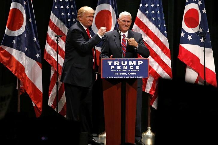 Republican presidential nominee Donald Trump brings vice presidential nominee Mike Pence onstage as he rallies with supporters in Toledo, Ohio, U.S., September 21, 2016. REUTERS/Jonathan Ernst/File Photo