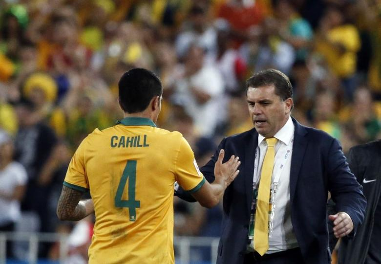 Australia's Tim Cahill (L) shakes hands with coach Ange Postecoglou as he is substituted during their Asian Cup final soccer match against South Korea at the Stadium Australia in Sydney in this January 31, 2015 file photo. REUTERS/Jason Reed