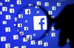 Un hombre con una lupa frente al logo de Facebook. 16 de diciembre de 2015. Facebook lanzó el lunes una versión empresarial de su aplicación móvil y sitio de internet, marcando la primera incursión de la red social en el muy competitivo escenario de software corporativo. REUTERS/Dado Ruvic/Illustration/File Photo