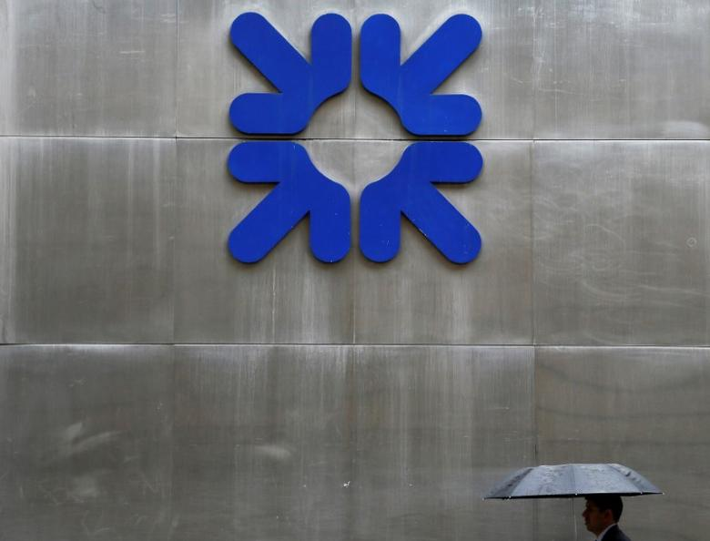 A man shelters under an umbrella as he walks past a branch of the Royal Bank of Scotland in London, Britain, September 17, 2013.    REUTERS/Stefan Wermuth/File Photo