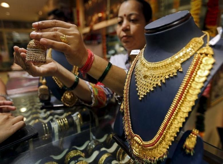 A saleswoman shows a gold earring to customers at a jewellery showroom in Mumbai, India, July 21, 2015.    REUTERS/Shailesh Andrade