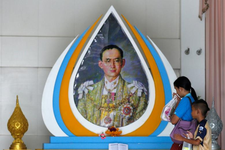 A well-wisher gestures in front of a picture of Thailand's King Bhumibol Adulyadej at Siriraj Hospital in Bangkok, Thailand, October 10, 2016.   REUTERS/Chaiwat Subprasom