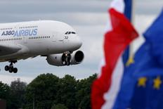 An Airbus A380, the world's largest jetliner, approaches to land after a flying display during the last day of the 51st Paris Air Show at Le Bourget airport near Paris, June 21, 2015. Also pictured are the French and the EU (R) flag. REUTERS/Pascal Rossignol