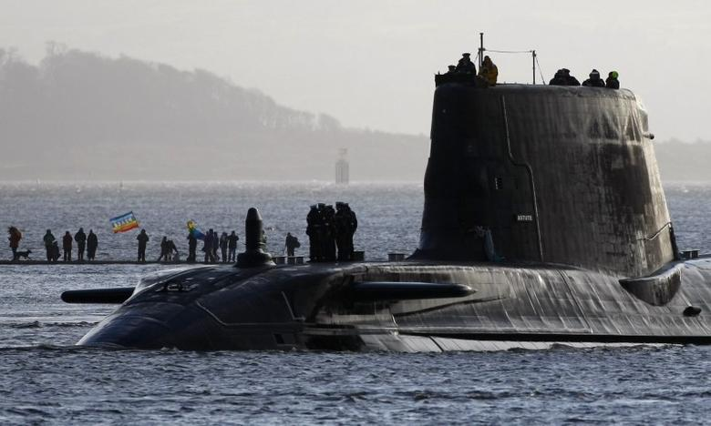 Peace protesters gather on a sand bank as the HMS Astute, a hunter-killer submarine, sails onto the River Clyde to its base in Faslane near Glasgow, Scotland, Nov. 20, 2009. REUTERS/David Moir