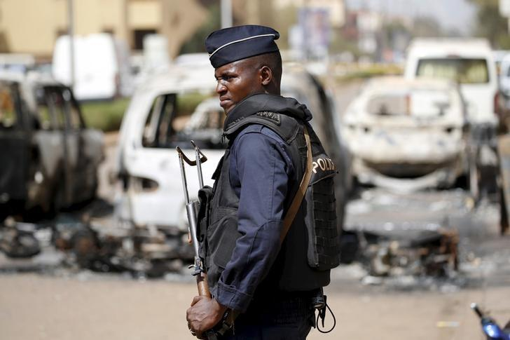A soldier stands guard in front of burned cars across the street from Splendid Hotel in Ouagadougou, Burkina Faso, January 17, 2016, REUTERS/Joe Penney