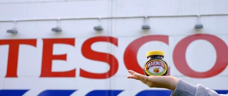 A woman holds a jar of Marmite, a Unilever brand, outside a Tesco store near Manchester, Britain October 13, 2016. REUTERS/Phil Noble