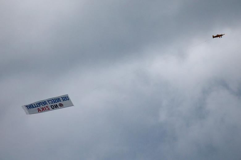 An airplane carrying a banner asking people to use insect repellent to avoid the Zika virus, flies over Miami, Florida, U.S., September 13, 2016. REUTERS/Carlo Allegri