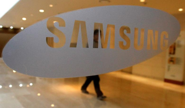 A man walks behind a logo of Samsung Electronics at the company's headquarters in Seoul April 30, 2010.  REUTERS/Jo Yong-Hak/File Photo