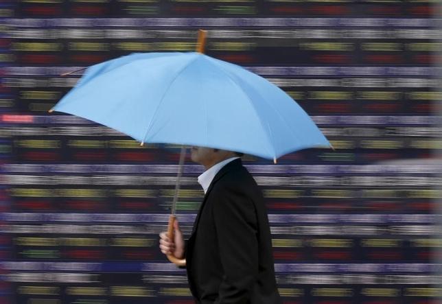 10月17日、今週の東京株式市場はレンジ取引となりそうだ。写真は株価ボードの前を通過する男性、昨年4月撮影(2016年 ロイター/Issei Kato)