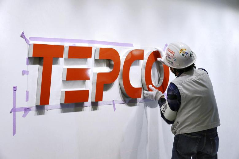 A worker puts up new logo of TEPCO Holdings and Tokyo Electric Power Company (TEPCO) Group on the wall at the TEPCO headquarters in Tokyo, Japan,  March 31, 2016. REUTERS/Masayuki Terazawa/Pool/File Photo