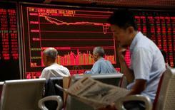 Инвесторы смотрят на электронное табло с данными об акциях в брокерской компании Пекина. Китайский фондовый рынок показал в понедельник сильнейший за последние три недели спад - настроения инвесторов ухудшились из-за обвала шанхайских акций класса В, номинированных в долларах США, на фоне продолжившегося ослабления юаня. REUTERS/Kim Kyung-Hoon/File Photo