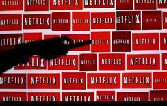 """Ilustración con un fondo de logos de Netflix.. 14 de octubre de 2014. Netflix Inc sumó muchos más suscriptores en el tercer trimestre que lo esperado por los analistas, debido al estreno de nuevos contenidos originales como """"Stranger Things"""". REUTERS/Mike Blake"""