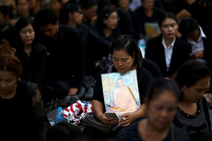 A mourner holds up a picture of Thailand's late King Bhumibol Adulyadej as she waits in line to offer condolences at the Grand Palace in Bangkok, Thailand, October 18, 2016. REUTERS/Athit Perawongmetha