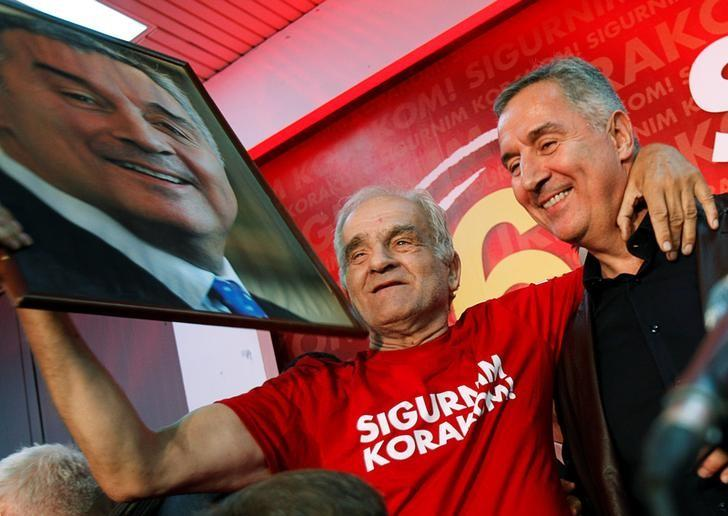 Montenegrin Prime Minister and leader of ruling Democratic Party of Socialist Milo Djukanovic (R) poses for a picture with a supporter during celebrations after parliamentary elections in Podgorica, Montenegro, October 17, 2016. REUTERS/Stevo Vasiljevic