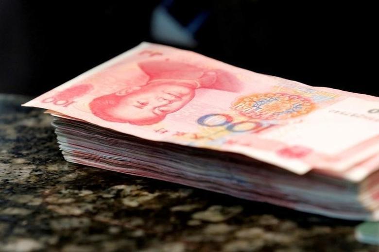 图为北京一家银行柜台上的一摞人民币。REUTERS/Kim Kyung-Hoon