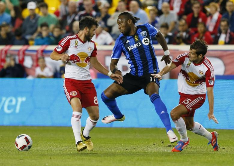 Sep 24, 2016; Harrison, NJ, USA; New York Red Bulls midfielder Felipe Martins (8) and Montreal Impact forward Didier Drogba (11) and New York Red Bulls midfielder Salvatore Zizzo (15) battle for the ball  during first half at Red Bull Arena. Mandatory Credit: Noah K. Murray-USA TODAY Sports