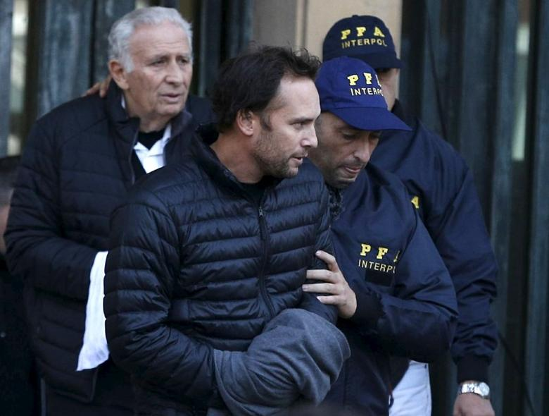 Argentine businessmen Mariano Jinkis (C) and his father Hugo (L, back) who are wanted by U.S. prosecutors in a FIFA bribery investigation, are escorted by police officers after they turned themselves in to authorities in Buenos Aires, Argentina, in this file photo dated June 18, 2015. REUTERS/Enrique Marcarian