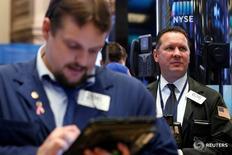 Трейдеры на торгах Нью-Йоркской фондовой биржи 21 октября 2016 года.  Американские фондовые индексы S&P 500 и Dow резко снизились в начале торгов пятницы, поскольку комментарии GE о ситуации в экономике и ее разочаровывающий прогноз оказали давление на акции промышленных компаний. Однако ралли акций Microsoft и McDonald's позволило сократить потери, и индекс Nasdaq торгуется без существенных изменений. REUTERS/Brendan McDermid