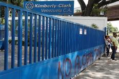 Рабочие у предприятия Kimberly-Clark в городе Маракай в Венесуэле. 10 июля 2016 года. Компания Kimberly-Clark Corp, производящая медицинскую продукцию и предметы личной гигиены, сообщила в понедельник о результатах за третий квартал, которые оказались ниже ожиданий из-за слабости валют стран Латинской Америки и снижения спроса на некоторые товары. REUTERS/Carlos Jasso