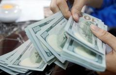 Un empleado de un banco cuenta dólares estadounidenses en una sucursal en Hanoi, Vietnam, 16 de mayo de 2016. El dólar se movía el lunes en torno a un máximo de casi nueve meses frente a una canasta de divisas, y contra el yen tocó un máximo de una semana, debido a las crecientes expectativas de que la Reserva Federal subirá sus tasas de interés en diciembre. REUTERS/Kham/Files