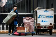 A man unloads parcels from a vehicle of a ZTO Express delivery in Beijing, China, October 27, 2016. REUTERS/Thomas Peter