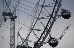 La economía de Reino Unido apenas se ralentizó en el tercer trimestre a pesar del sorprendente voto a favor del brexit, lo que disminuye las posibilidades de un recorte de los tipos de interés del Banco de Inglaterra la próxima semana. En la imagen, unas grúas junto al London Eye en Londres, el 27 de octubre de 2016. REUTERS/Toby Melville