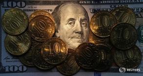Десятирублевые монеты на стодолларовой купюре. Санкт-Петербург, 22 октября 2014 года. Рубль показывал в основном отрицательную динамику на торгах пятницы, копируя поведение нефтяных цен и отражая сокращение объемов продаж экспортной выручки в конце налогового периода. REUTERS/Alexander Demianchuk