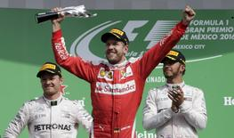 Formula One - F1 - Mexican F1 Grand Prix - Mexico City, Mexico - 30/10/16 - Third placed finisher Ferrari driver Sebastian Vettel of Germany celebrates as second placed finisher Mercedes driver Nico Rosberg of Germany (L) and his teammate, race winner Lewis Hamilton of Britain, look on. REUTERS/Henry Romero