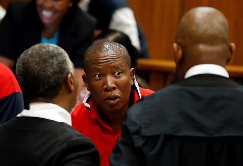 Julius Malema (C), president of the Economic Freedom Fighters (EFF), reacts as he speaks to Adv Dumisa Ntsebeza (L) and Advocate Dali Mpofu during a court hearing arguments on a report into allegations of political interference by wealthy friends of President Jacob Zuma, at the North Gauteng High Court, in Pretoria, South Africa. November 2, 2016.  REUTERS/Siphiwe Sibeko