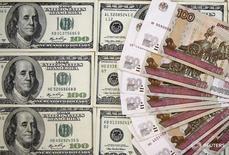 Рублевые и долларовые купюры в Сараево 9 марта 2015 года. Рубль торгуется в минусе утром среды, но отбил потери начала дня против доллара, поскольку победивший на американских выборах кандидат от республиканской партии Дональд Трамп обещал в случае своей победы улучшить отношения c Россией. REUTERS/Dado Ruvic