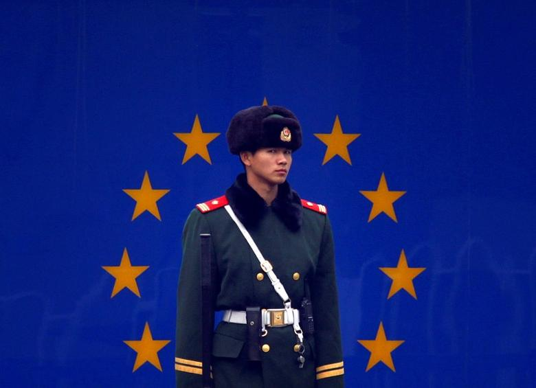A paramilitary policeman stands guard at the entrance to the European Union embassy in central Beijing, China December 13, 2011. REUTERS/David Gray/File Photo