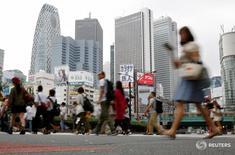 Люди переходят дорогу на фоне небоскребов в Токио 29 сентября 2016 года. Рост экономики Японии в период с июля по сентябрь превысил ожидания рынка, ускорившись третий квартал подряд благодаря увеличению экспорта, однако слабая активность внутри страны вызывает сомнения в отношении устойчивости экономического восстановления. REUTERS/Toru Hanai