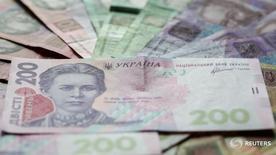 Купюры валюты гривна в Киеве 6 августа 2014 года. Национальный банк Украины назвал одной из причин усиления волатильности на валютном рынке обострение политической напряженности в стране, но выразил уверенность, что новые факторы давления на гривну не будут долгосрочными. REUTERS/Konstantin Chernichkin