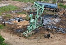 Нефтяной насос на месторождении компании Oil and Natural Gas Corp's (ONGC) рядом с Ахмадабадом, Индия. Цены на нефть снизились в среду на данных о превзошедшем прогнозы росте запасов в США, что оказало давление на и без того перенасыщенный рынок.   REUTERS/Amit Dave