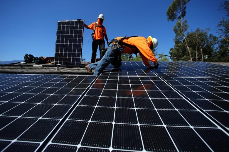 Solar installers from Baker Electric place solar panels on the roof of a residential home in Scripps Ranch, San Diego, California, U.S. October 14, 2016. REUTERS/Mike Blake - RTX2QGWW