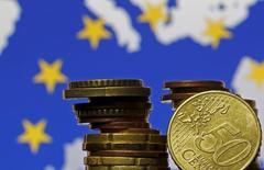 Monedas de euro frente a una bandera de la Unión Europea, 28 de mayo, 2015. Dos consorcios, que incluyen a la firma japonesa de ingeniería JGC Corp y a la francesa de servicios petroleros Technip, han sido preseleccionadas para realizar la renovación valorada en unos 680 millones de dólares de una refinería en Aruba, según dijeron a Reuters tres fuentes cercanas al acuerdo.  REUTERS/Dado Ruvic