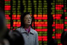 Una inversora observa una pantalla electrónica que muestra información de acciones en una casa de valores en Shanghái, China, 9 de noviembre del 2016. Las acciones chinas avanzaron levemente el jueves, cortando una racha de dos sesiones de caídas, luego de que las ganancias de los papeles ligados a la infraestructura contrarrestaron la debilidad del sector de materias primas.REUTERS/Aly Song