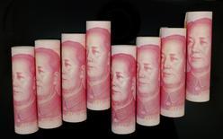 Composición de billetes de 100 yuanes. 5 noviembre 2013. Las autoridades chinas han asistido impávidas a la reciente depreciación del yuan, pero están listas para frenar su caída por temor a provocar una salida de capitales si la divisa se desvaloriza demasiado rápido a menos del nivel psicológico de 7 unidades por dólar, dijeron asesores. REUTERS/Jason Lee