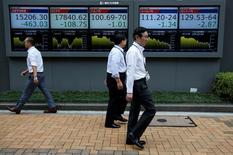 Peatones caminan frente a unas pantallas que muestra el índice Nikkei y otras divisas afuera de una correduría en Tokio, Japón. 6 de julio de 2016. El índice Nikkei de la bolsa de Tokio subió el viernes por séptima sesión consecutiva tras un repunte de las acciones en Estados Unidos y en medio de la fortaleza del dólar frente al yen. REUTERS/Issei Kato