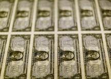 Billetes de 1 dólar sobre una mesa de luz en la Casa de la Moneda de los Estados Unidos en Washington, nov 14, 2014.El dólar retrocedía el viernes frente a otras importantes monedas, ya que los inversores aprovechaban el descenso en los rendimientos de los bonos del Tesoro y la pausa por un feriado en Estados Unidos para consolidar los avances que han impulsado al billete verde a máximos de casi 14 meses. REUTERS/Gary Cameron/File Photo