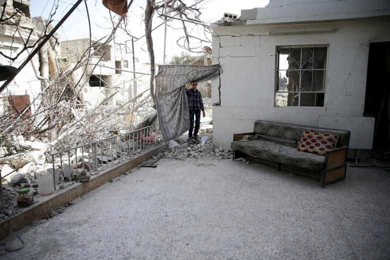 A boy inspects a damaged house in the rebel-held besieged city of Douma, a suburb of Damascus, Syria February 27, 2016. REUTERS/Bassam Khabieh